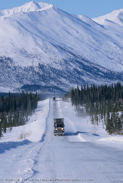 Semi truck hauls supplies to Prudhoe Bay Oil fields on the snow covered James Dalton Highway, Brooks range, Arctic, Alaska