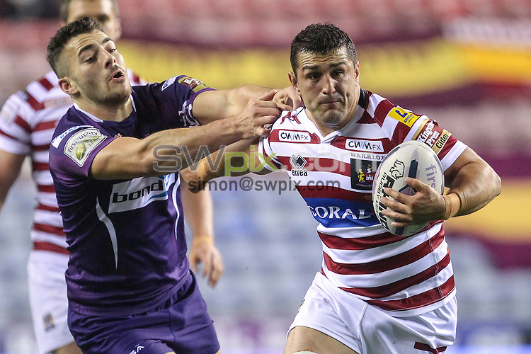 Picture by Alex Whitehead/SWpix.com - 01/10/2015 - Rugby League - First Utility Super League - Wigan Warriors v Huddersfield Giants - DW Stadium, Wigan, England - Wigan's Ben Flower escapes the tackle of Huddersfield's Jake Connor.