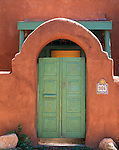 Arched adobe entrance and green doors, Santa Fe, New Mexico