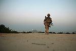As dawn breaks, an interpreter for Canadian soldiers walks across the roof of a compound in the village of Zalakhan in Kandahar province, Afghanistan. He has just announced over a loudspeaker that any Taliban fighters in the village should leave or be killed. Aug. 6, 2009 DREW BROWN/STARS AND STRIPES
