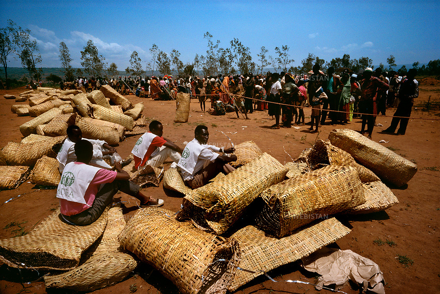 1994. Burundi. Lake Cyohoha. Maza Camp. During the Rwandan Genocide, refugees wait for food distribution that will be given in large wicker bags. Burundi. Lac Cyohoha. Camp de Maza. Pendant le génocide au Rwanda, des réfugiés attendent une distribution de nouriture qu'on leur donnera dans des grands sacs en osier.