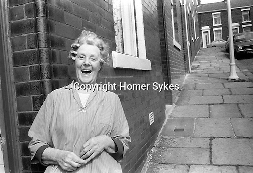 Working class white woman in hair curlers standing outside her terraced house laughing Blackburn Lancashire 1983.