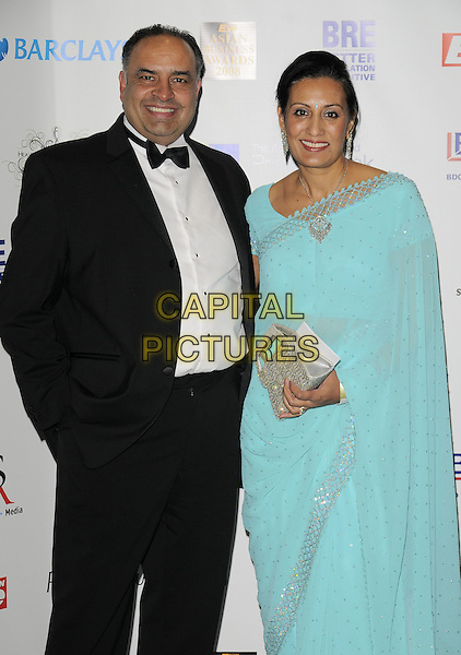 GUEST & KAMEL HOTHI.The Eastern Eye Asian Business Awards, Bobby Moore Room, Wembley Stadium, Wembley, London, England..November 19th, 2008.half 3/4 length black tuxedo blue sari dress silver trim clutch bag .CAP/CAN.©Can Nguyen/Capital Pictures.
