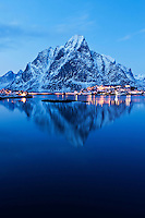 Olstind mountain peak rises above Reine in evening light, Lofoten islands, Norway