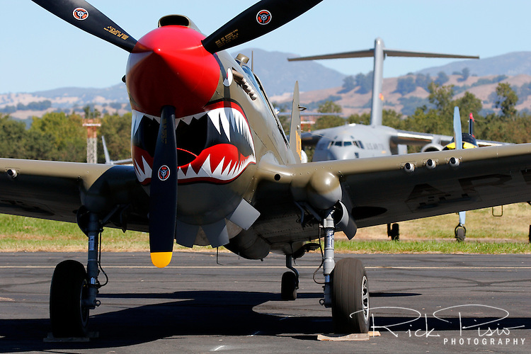 A 1940's era P-40 Warhawk sits on the ramp at the Charles M. Schulz Regional Airport in Santa Rosa, California during the 2007 Wings Over the Wine Country Airshow. An Airforce C-17 Globemaster III, the US Air Forces's most modern transport plane sits in the background.  The Wings Over the Wine Country Airshow is held annually during the month of August and sponsored by the Pacific Coast Air Museum. Photographed 08/07