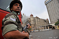 An Indian soldier takes cover behind a fire truck while The Taj Mahal hotel burn during the final gun battle between the Indian commandos and  militants inside the hotel in the early hours of 29th of November 2008 in Mumbai, India.