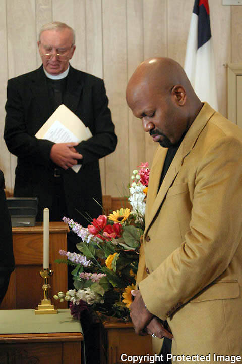 Rev. Mark Griffin of Wayman Chapel AMC, front, and The Rev. Dr. Richard M. Turk of St. Andrew Episcopal Church, pray during the ceremony honoring Martin Luther King, Jr. Sunday at St. Andrew Methodist Episcopal Church in Jacksonville Beach. Photo by Maggie FitzRoy/staff
