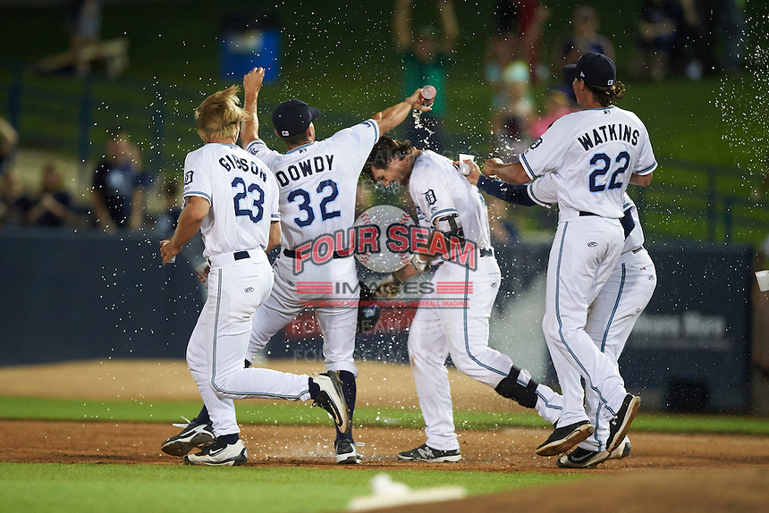 West Michigan Whitecaps first baseman Will Allen (16) is doused with water by teammates Cam Gibson (23), Kyle Dowdy (32), Jose Zambrano (hidden), and Spenser Watkins (22) after a game winning base hit during a game against the Burlington Bees on July 25, 2016 at Fifth Third Ballpark in Grand Rapids, Michigan.  West Michigan defeated Burlington 4-3.  (Mike Janes/Four Seam Images)