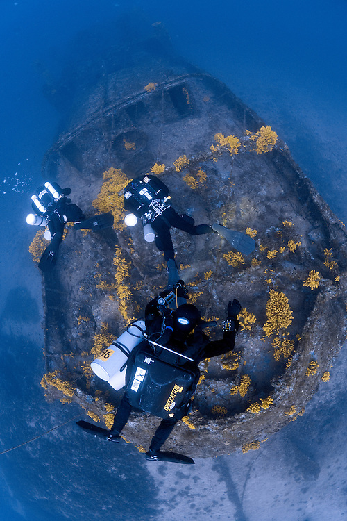 Divers exploring the wreck of the Ursus which lies between at 60 metres