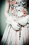 Young woman with short brown hair wearing floral period party dress and gloves holding necklace