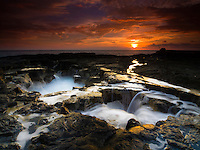 Water surges in and out of this large hole along the lava rock shoreline during a dramatic sunset at Keahole Point, Big Island.