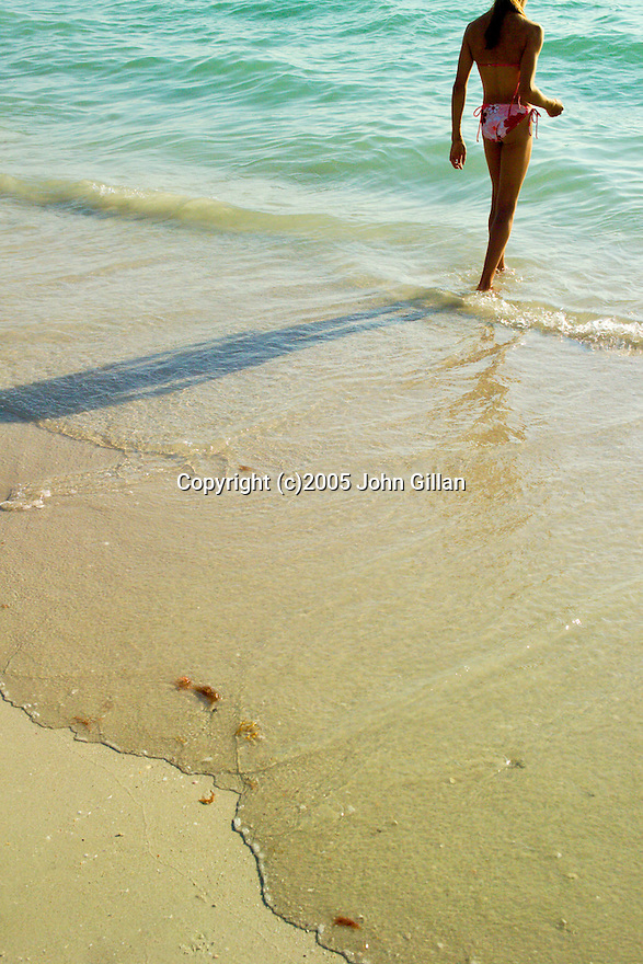 Girl in bikini standing at the shore line of the beach with waves coming up on the sand. D3DW1037
