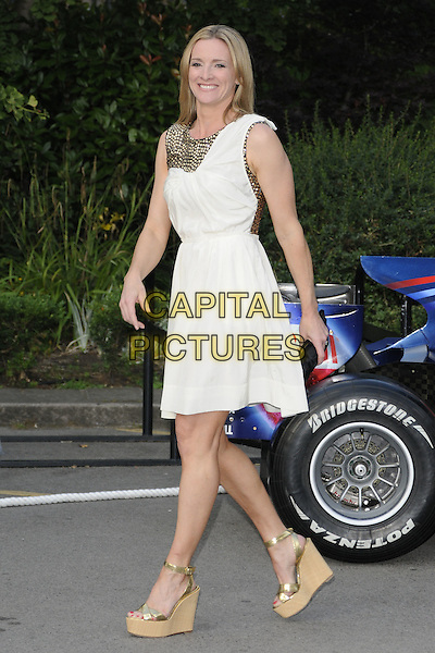 GABBY LOGAN.The F1 Party held at the Natural History Museum, London, England, UK..5th July 2010.Formula one full length white cream gold grecian dress beaded embellished studded platform ankle strap shoes clutch bag wedges side walking.CAP/CAN.©Can Nguyen/Capital Pictures.