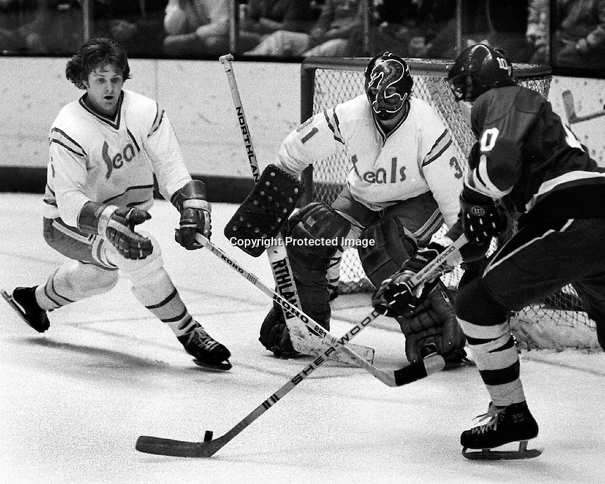 Seals hockey action, Len Frig and goalie Gary Simmons defend against Penguins #10 Pierre Larouche.  1976 photo/Ron Riesterer