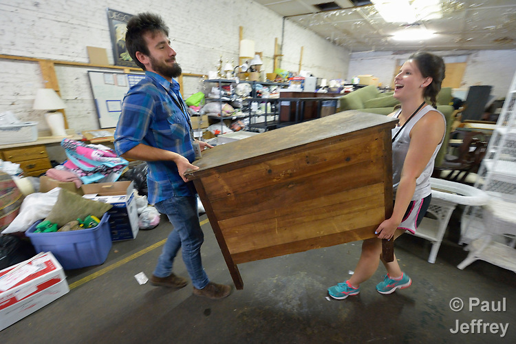Josh Digrugilliers and Emilie MacDonald load furniture in a Church World Service warehouse in Lancaster, Pennsylvania. They are furnishing the apartment of a refugee family about to arrive in the United States.<br /> <br /> Photo by Paul Jeffrey for Church World Service.