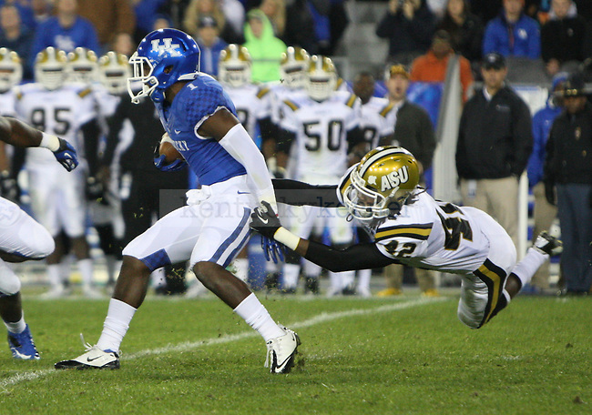 UK running back Ryan Timmons (1) runs the ball forward as Alabama State safety Nathaniel Black (42) attempts to tackle him during the University of Kentucky Homecoming football game against Alabama State at Commonwealth Stadium in Lexington, Ky., on Saturday, November 2, 2013. Photo by Tessa Lighty | Staff