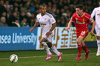 SWANSEA, WALES - MARCH 16: Wayne Routledge of Swansea (L) looks out for a team mate to pass the ball to, marked by Joe Allen of Liverpool (R) during the Premier League match between Swansea City and Liverpool at the Liberty Stadium on March 16, 2015 in Swansea, Wales