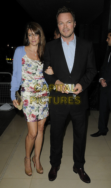 CAROLINA ACOSTA & PETE TONG.'An Evening at the Sanderson' celebrating 10 years, at the Sanderson Hotel, London, England. .April 27th 2010.full length black suit white blue red floral print dress cardigan arms linked couple CAP/CAN.©Can Nguyen/Capital Pictures.