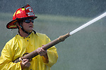 A firefighter spraying water from a hose line