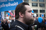 A man with a beard standing under a banner before a demonstration by the Alternative für Deutschland (AfD) political party in Berlin. Around 5000 supporters of the AfD took part in the march and rally through central Berlin calling on German Chancellor Angela Merkel to halt the influx of refugees into the country. Around one million refugees from the Middle East and north Africa arrived in Germany during 2015, 50,000 of whom came to Berlin.