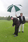 South Kerry Independent Candidate Jackie Healy-Rae was playing around while on a visit to Kenmare Golf Club on Wednesday where Risteard O'Lionaird was on hand to give the deputy a bit of cover from the heavy rain.<br />Picture by Don MacMonagle