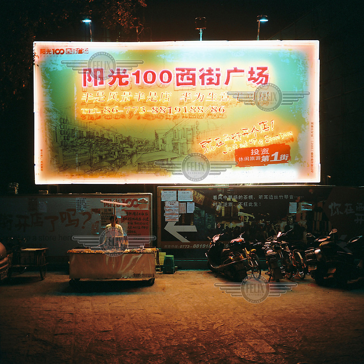 A woman prepares food under an advertising billboard on a market street in Guilin.