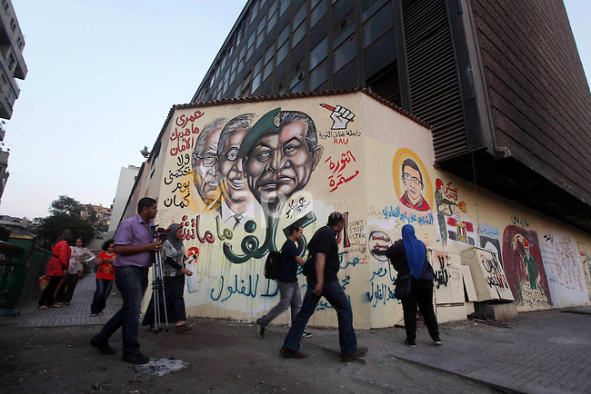Egyptians walk in front of a wall sprayed graffiti at Tahrir Square in Cairo May 30, 2012. An arson attack on the headquarters of one of the two candidates in Egypt's presidential election has marred campaigning for the second round in a vote that has polarised the nation with the choice of an Islamist or Hosni Mubarak's last prime minister. Photo by Ashraf Amra