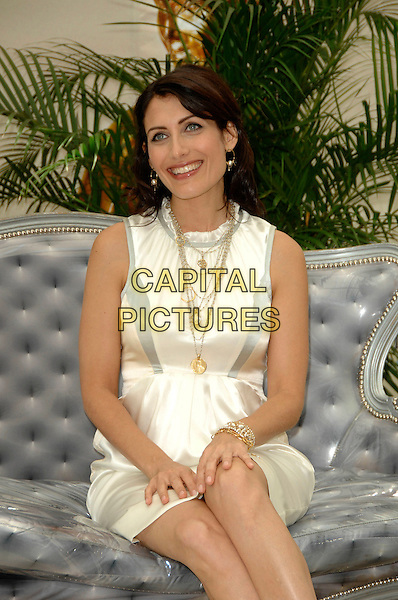 "LISA EDELSTEIN.Photocall promoting the television series ""House"" on the fourth day of the 2008 Monte Carlo Television Festival held at Grimaldi Forum, Monaco, Principality of Monaco..June 11th, 2008.half 3/4 length white cream sleeveless silk satin dress sitting couch sofa gold necklaces .CAP/TTL .© TTL/Capital Pictures"