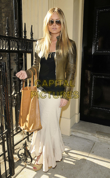 Sarah Barrand.The Twiggy for M&S Woman 1st collection of 2012 launch party, Home House, Portman Square, London, England..April 12th, 2012.full length brown leather jacket black top skirt white beige bag purse sunglasses shades .CAP/CAN.©Can Nguyen/Capital Pictures.