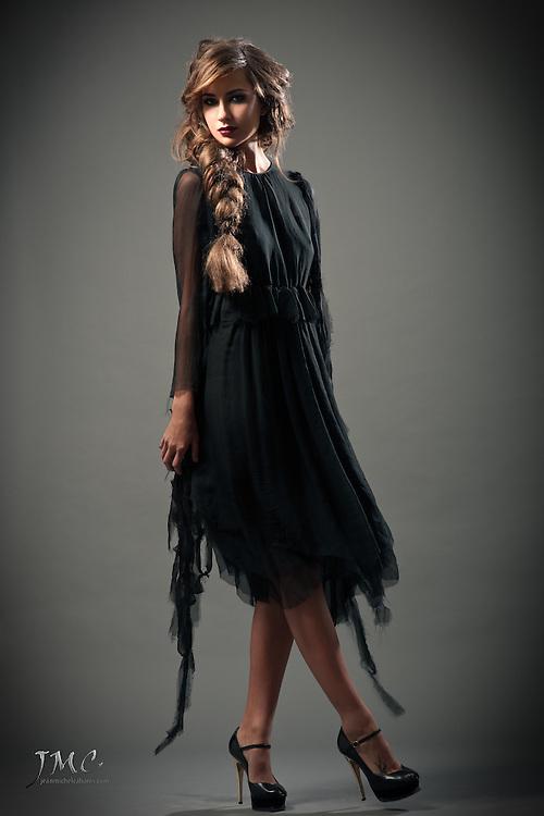 Beautiful brunette fashion model in black dress and black heels, on grey background