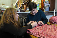 STAFF PHOTO FLIP PUTTHOFF<br /> HAND-MADE GIFT<br /> Elizabeth Hamrin, left, helps Rita House with a knitting project on Saturday Dec. 27 2014 at The Rabbit's Lair fabric and needlecraft store in downtown Rogers. House said she's making a sweater for her granddaughter.
