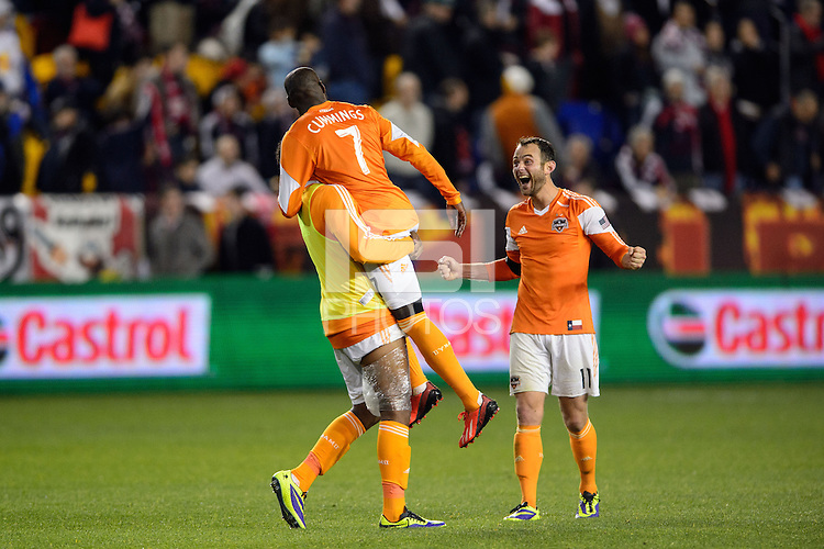 Giles Barnes (23) of the Houston Dynamo carries Omar Cummings (7) and celebrates with Brad Davis (11) after defeating the New York Red Bulls. The Houston Dynamo defeated the New York Red Bulls 2-1 (4-3 on aggregate) in overtime of the second leg of the Major League Soccer (MLS) Eastern Conference Semifinals at Red Bull Arena in Harrison, NJ, on November 6, 2013.