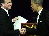 U.S. President Barack Obama (R) shakes hands as he hosts British Prime Minister David Cameron (L) and his wife Samantha Cameron for a state dinner at the South Lawn of the White House March 14, 2012 in Washington, DC. Prime Minister Cameron was on a three-day visit in the U.S. and he had talks with President Obama earlier the day.  .Credit: Alex Wong / Pool via CNP