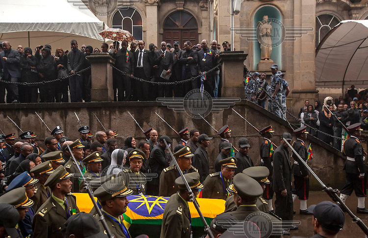 Dignitaries and mourners watch as the coffin of Prime Minister Meles Zenawi, draped in the Ethiopian flag, is carried by army officers through Addis Ababa.