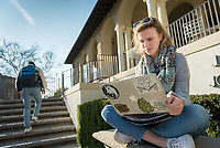 Student using a laptop outside the JSC Branca Patio and the Green Bean. Jan. 26, 2017.<br />