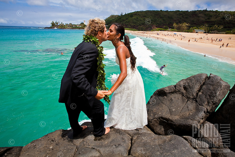 Couple in wedding attire kissing on the Waimea jump rock before jumping off together