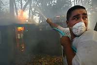Angel Castillo struggles against smoke as his families home on South Mountain Road, South of Santa Paul, is threatened by fire. Castillo fights smoke as fire consumes the families guest house. 45,000 acres have burned from Piru to Moorpark and Simi Valley.