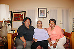 Lisa McNair (right to left) sits next to her mother Maxine and sister Kimberly Brock in her Birmingham, Alabama home August 13, 2013. Lisa's sister Denise McNair was the youngest victim who died in a bomb blast at 16th Street Baptist Church September 15, 1963.