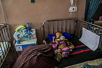 KABUL, AFGHANISTAN - SEPTEMBER 21: A mother lays with her malnourished child, receiving treatment at the Indira Gandhi Children Hospital on September 21, 2013 in Kabul, Afghanistan.