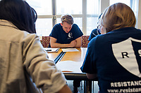 """Sam Carson (center), 28, a Master in Public Policy graduate student at Harvard, leads the Resistance School logistics group volunteer meeting before a session of Resistance School in the Taubman Building of Harvard University's John F. Kennedy School of Government, on Thurs., April 27, 2017. The goal of the meeting was to plan how to direct attendees from the registration location to the lecture location. Resistance School was started by progressive graduate students at Harvard after the Nov. 8, 2016, election of President Donald Trump. Resistance School describes itself as a """"practical training program that will sharpen the tools [needed] to fight back at the federal, state, and local levels."""" Resistance School puts on live lectures by leading progressives that are streamed and archived online alongside other information on the Resistance School website. During the lectures, teams of volunteers engage with followers on social media, including Facebook and twitter, sharing soundbytes, quotations, and supplementary materials as the lectures happen."""