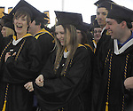 (Framingham 051913)  Ashley Roy of Groton,  center, dances to the bag pipes being played at the start of the commencement ceremony at Framingham State University.  Reacting are,  Amber Pierce of Franklin and William Sanderson of Amesbury. (Jim Michaud Photo)