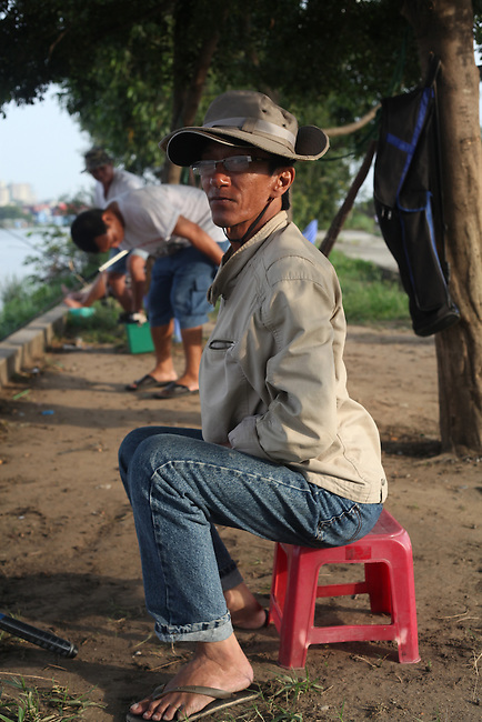 A fisherman sits on the bank of the Saigon River one afternoon outside Ho Chi Minh City, Vietnam. Sept. 1, 2011