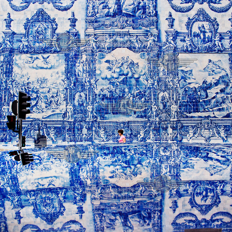 A woman walks past the blue Azulejo tiles which depict different Christian scenes, reflected on the roof of a car in the foreground.