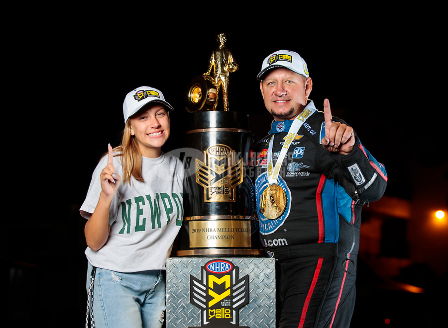 Nov 17, 2019; Pomona, CA, USA; NHRA funny car driver Robert Hight and daughter Autumn Hight pose for a portrait with the championship trophy after clinching the 2019 funny car world championship during the Auto Club Finals at Auto Club Raceway at Pomona. Mandatory Credit: Mark J. Rebilas-USA TODAY Sports
