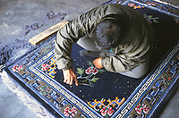 Man trimming carpets at the Tibetan Handicraft Center.
