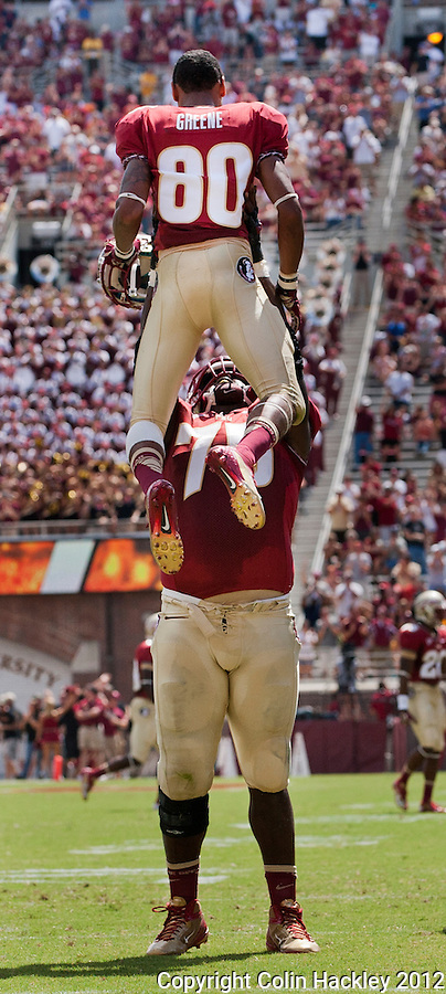 TALLAHASSEE, FL 9/15/12-FSU-WAKE091512 CH-Florida State's Rashad Greene is hoisted high by Cameron Erving after Greene ran a punt back for a touchdown during first half action against Wake Forest Saturday at Doak Campbell Stadium in Tallahassee. The Seminoles shut out the Demon Deacons 52-0..COLIN HACKLEY PHOTO