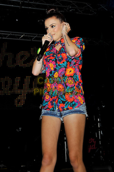 Cher Lloyd.Performing at Perez Hilton's 'One Night In London', The Electric, Brixton, London, England, UK, 13th July 2012..music concert gig live on stage half length red print  pink floral top  green wrist watch denim shorts  hair up bun hoop earrings  studded white tattoo microphone 3/4 singing .CAP/MAR.© Martin Harris/Capital Pictures.