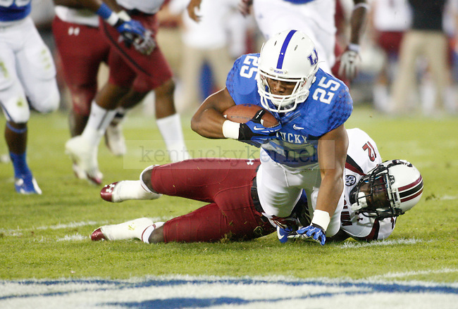 Kentucky Wildcats running back Jonathan George (25) is tackled at the University of Kentucky football vs.  South Carolina at Commonwealth Stadium in Lexington, Ky., on Saturday, September 29, 2012. Photo by Tessa Lighty | Staff