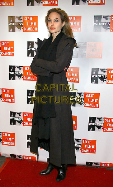 ANGELINA JOLIE.At the benefit gala and concert to benefit WITNESS, New York, NY. .December 5th, 2005.Photo: Jackson Lee/AdMedia/Capital Pictures.Ref: JL/ADM.full length arms crossed black coat .www.capitalpictures.com.sales@capitalpictures.com.© Capital Pictures.