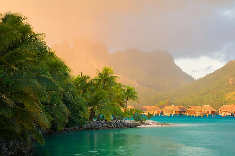 Sunrise and bungalows with lagoon. Bora Bora. French Polynesia.